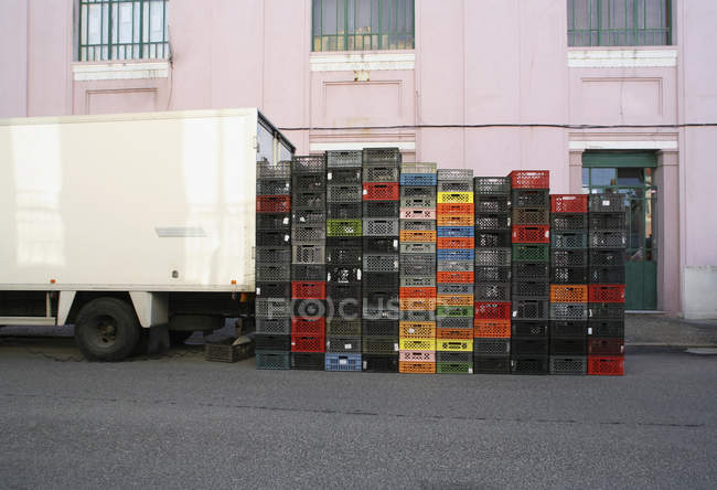 Stack of crates next to delivery truck at street — Stock Photo