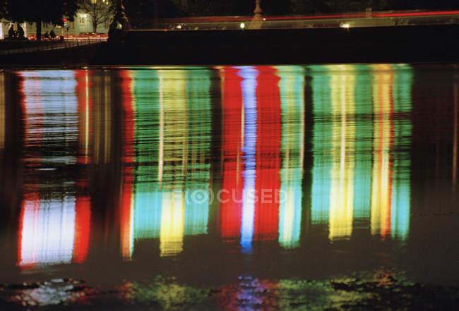 Multi різнокольорових вогників дзеркальне відображення у воді на ніч — стокове фото