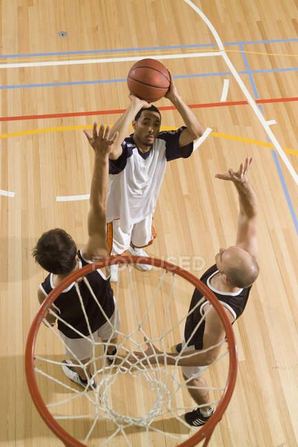 Tre giovani uomini giocare a basket — Foto stock