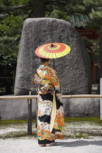 Задній вид жінки носять кімоно читання гравіювання камінь — стокове фото