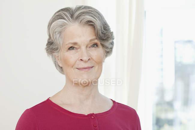 Portrait d'une femme senior souriante devant la fenêtre — Photo de stock
