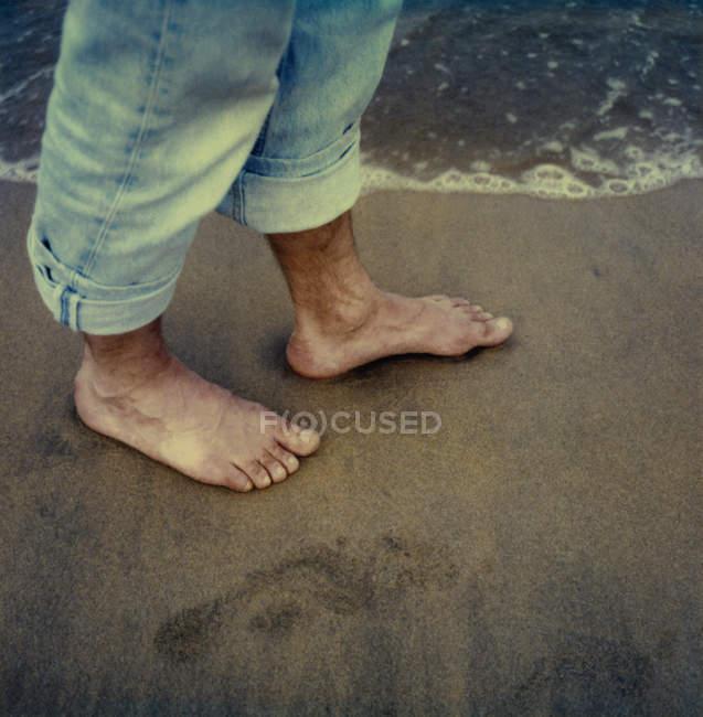 Männliche nackte Füße am Sandstrand — Stockfoto