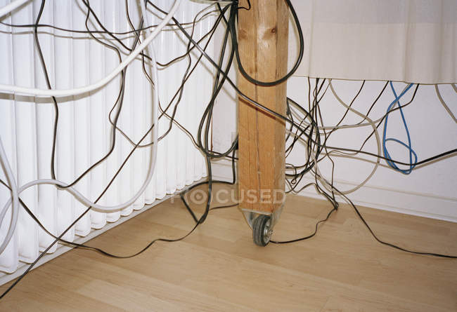 Cabos desarrumado pendurado por baixo da mesa — Fotografia de Stock