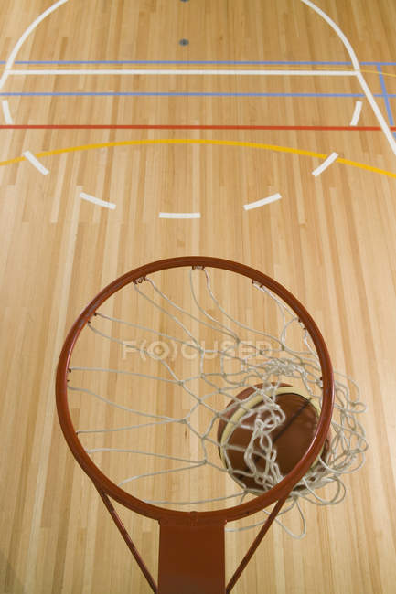 From above basketball falling through hoop on background of free throw line — Stock Photo