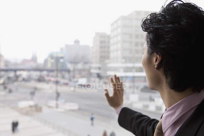 Un uomo d'affari che guarda attraverso una finestra — Foto stock