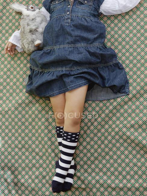 Низкая часть молодая девушка, лежа на узорной лист withtoy — стоковое фото