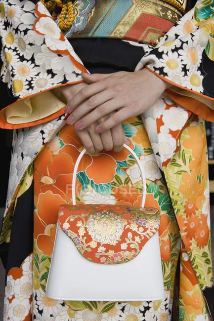 Midsection de mulher vestindo kimono segurando bolsa — Fotografia de Stock