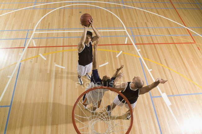 Трое юношей играют в баскетбол — стоковое фото