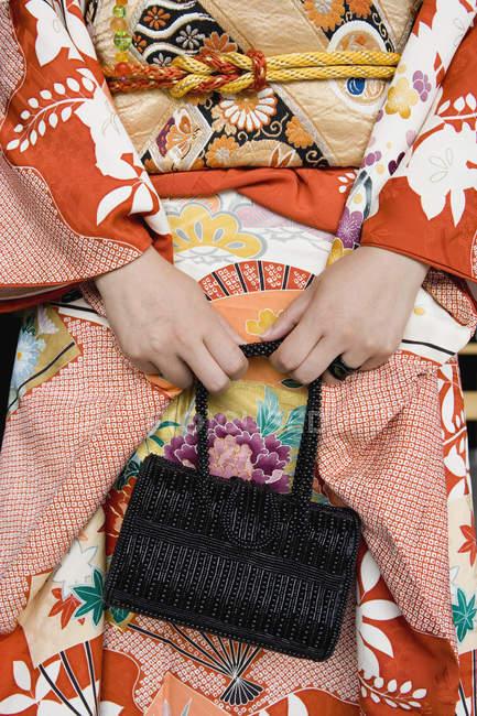 Midsection de mulher vestindo quimono e segurando bolsa — Fotografia de Stock