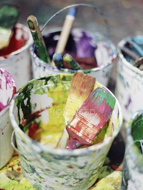 Baldes de plástico bagunçado de tinta e pincéis — Fotografia de Stock