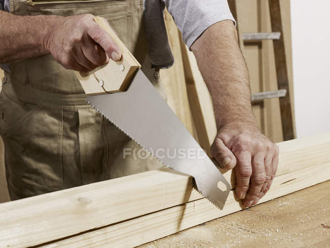Midsection of man sawing wood — Stock Photo