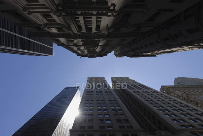 Bottom view of skyscrapers facades over blue sky — Stock Photo
