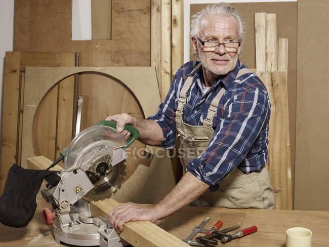Человек пилит дерево в мастерской и смотрит в сторону — стоковое фото
