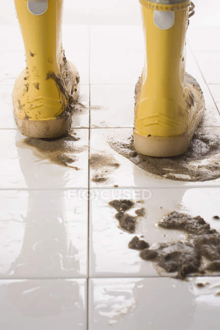 Close up view of pair of muddy rubber boots on white tiled floor — Stock Photo