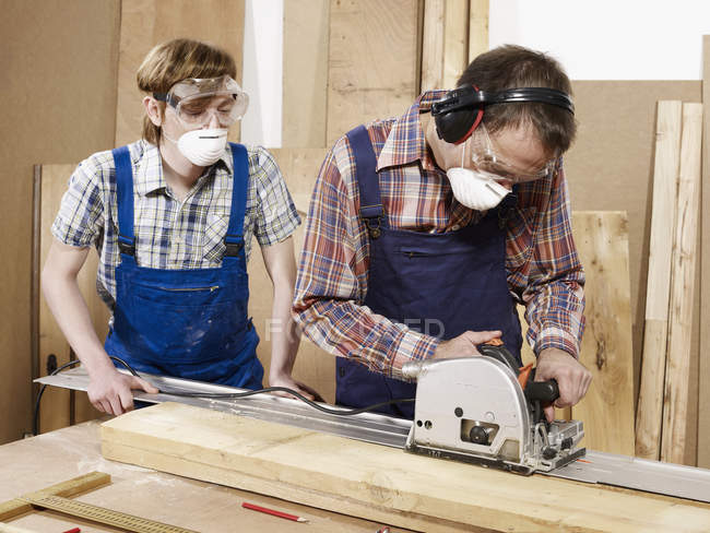 Two men in protective workwear cutting wood in workshop — Stock Photo