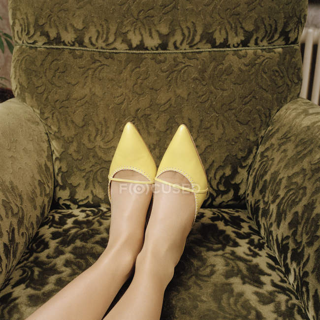 Crop woman wearing high heel shoes and with her feet up on an armchair — Stock Photo