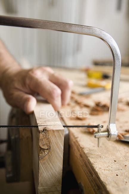 Close up view of carpenter sawing plank at workbench — Stock Photo