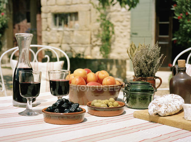 Outdoor table set with wine and appetizers — Stock Photo