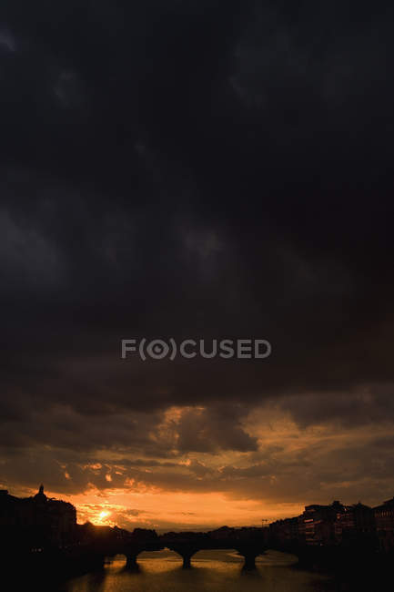 Moody sky at sunset over bridge silhouette — Stock Photo