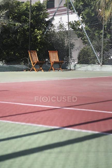 Espreguiçadeiras à beira do campo de ténis vazio — Fotografia de Stock