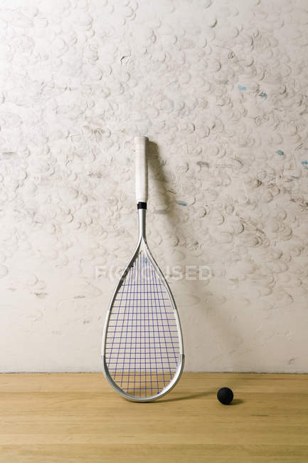 Squash racket leaning on wall by ball on floor — Stock Photo