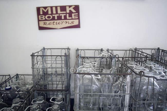 Stacked crates empty milk bottles — Stock Photo