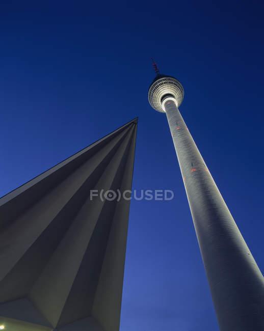 Vue du dessous de la tour de télévision allumé au crépuscule de la nuit — Photo de stock