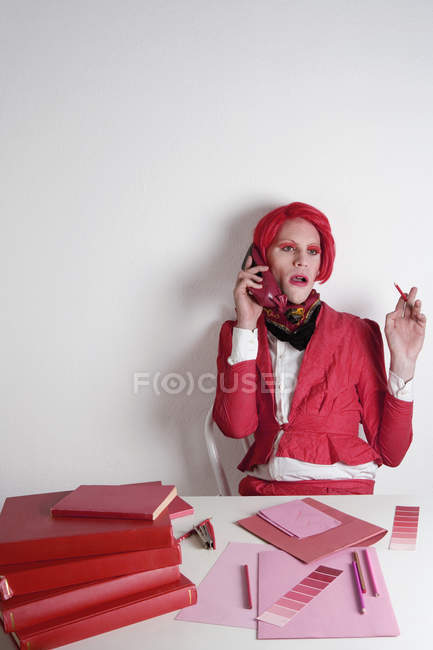 Drag Queen sitting at desk with red color swatch on the phone — стоковое фото