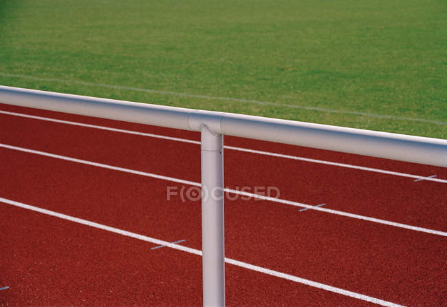 Railing next to empty running tracks and field — Stock Photo