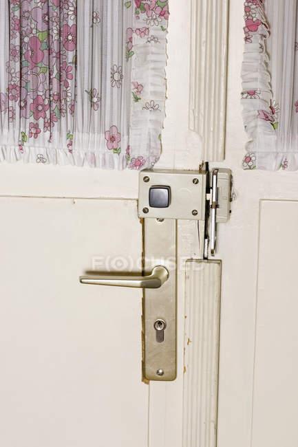 Крупним планом вид на задні двері дверна ручка і штори з квітковим візерунком — стокове фото