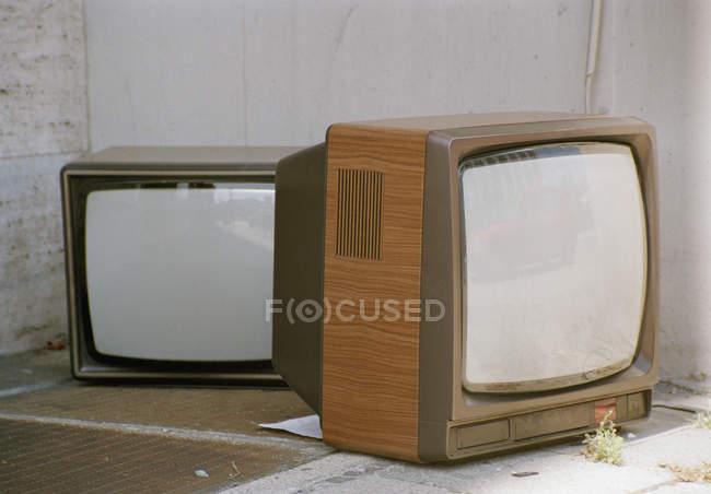 Télévision vintage deux ensembles gauche sur trottoir — Photo de stock