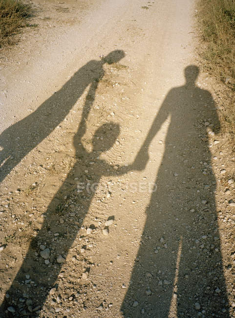 Shadow of family holding hands on rural road — Stock Photo