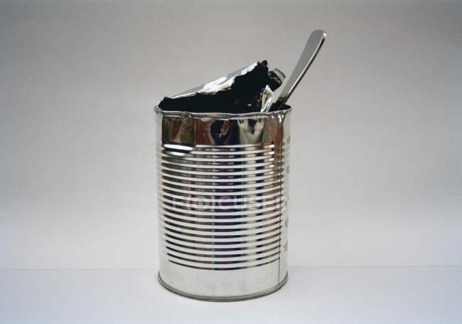 Scatola di latta aperta con cucchiaio su sfondo bianco — Foto stock