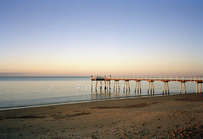 Tranquil seascape with pier over sunset gradient sky — Stock Photo