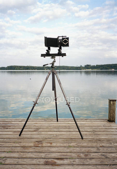 Old fashioned camera on tripod at jetty on lake — Stock Photo