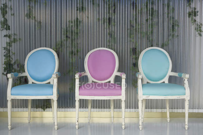 Three ornate chairs in row over ivy-embraced wall — Stock Photo