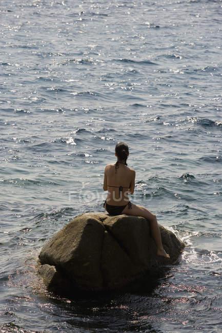 Visão traseira da mulher sentada na rocha no mar — Fotografia de Stock
