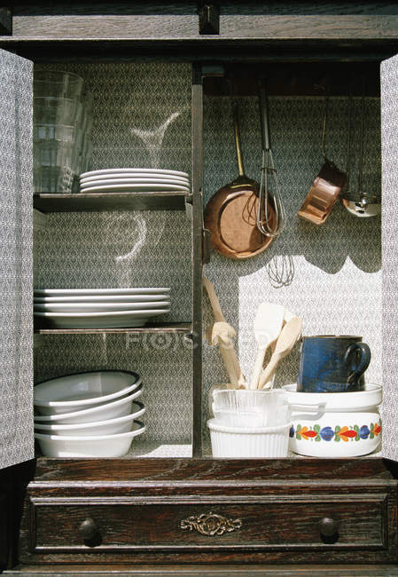 Cookwear and crockery in open cabinet — Stock Photo