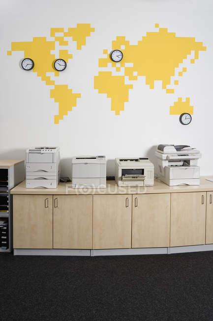 Fotocopiadoras de la fila por pared con mapamundi y relojes - foto de stock