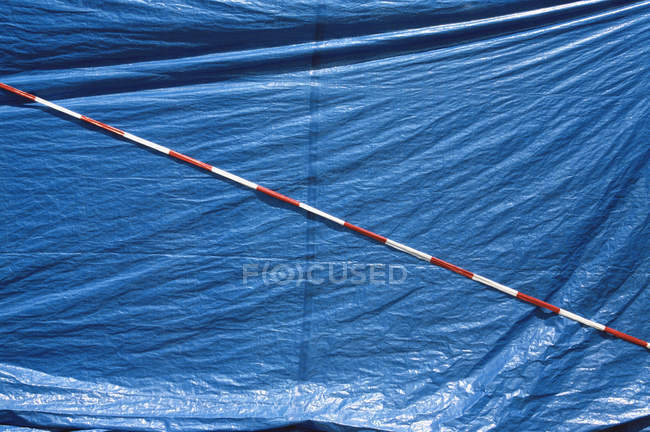 Full frame shot of blue tarpaulin and striped cordon tape — Stock Photo