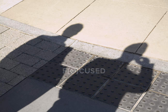Shadow of two people on street pavement — Stock Photo