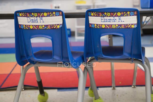 Dos sillas vacías con etiquetas de nombres en la escuela primaria - foto de stock