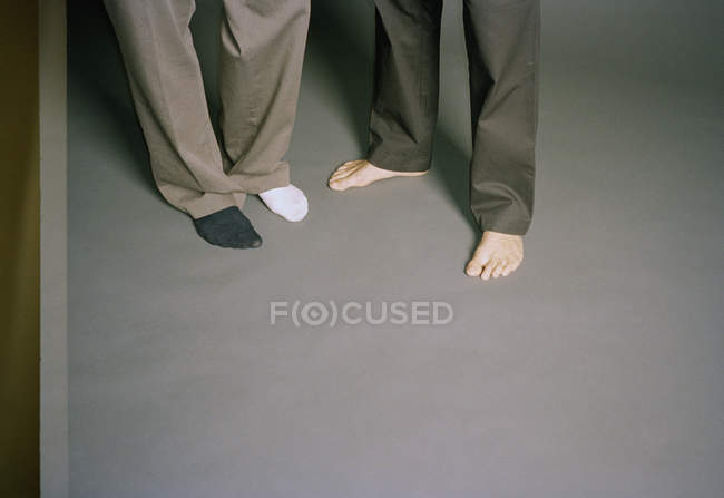 Низкая часть босоногого мужчины, стоящего рядом с человеком в разных носках — стоковое фото