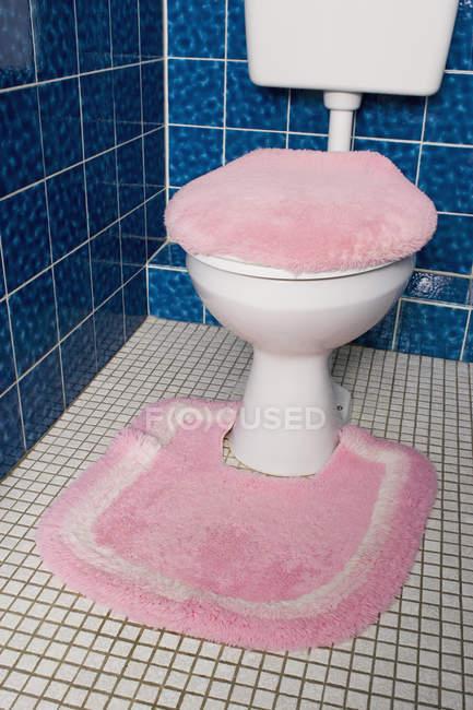 Туалет з пухнастим рожевий накидка і килим — стокове фото