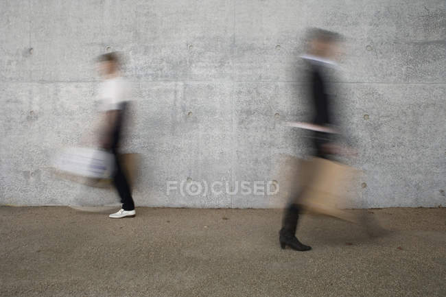 Shot of blurred people walking past wall — Stock Photo