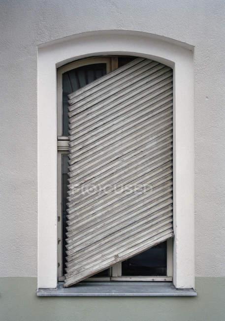 Kaputte Fensterläden hängen schräg am Fenster — Stockfoto