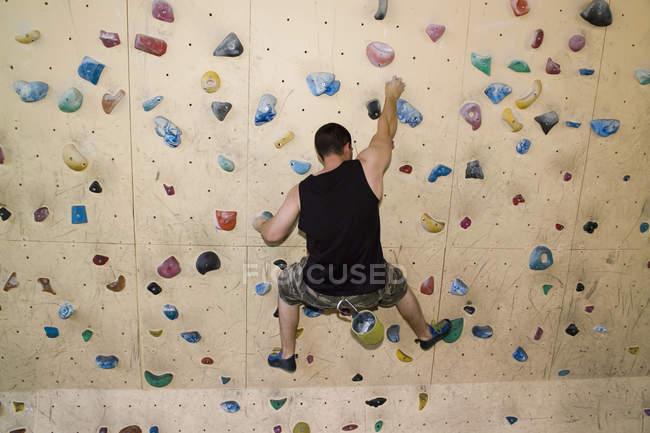 Rückansicht des Menschen üben Klettern indoor — Stockfoto