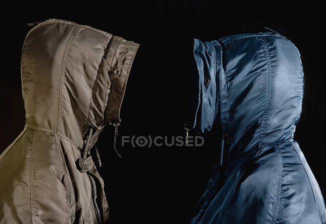 Side view of two men wearing hooded parkas standing face to face — Stock Photo