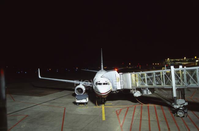 Passarela de passageiro ligada ao avião à noite — Fotografia de Stock
