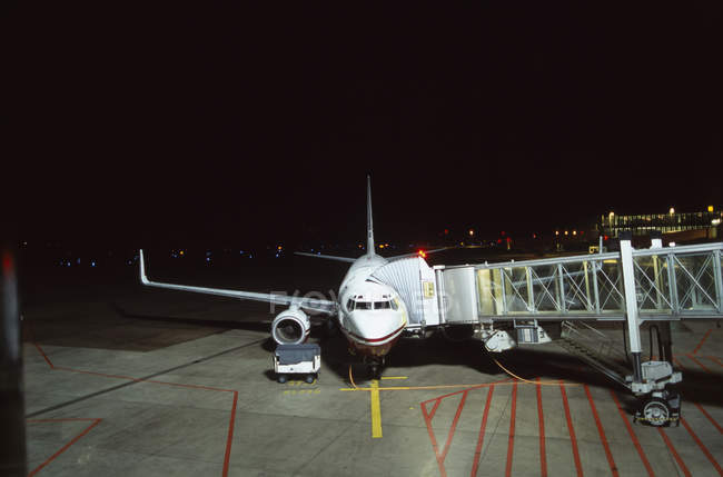 Passagiersteg nachts mit Flugzeug verbunden — Stockfoto